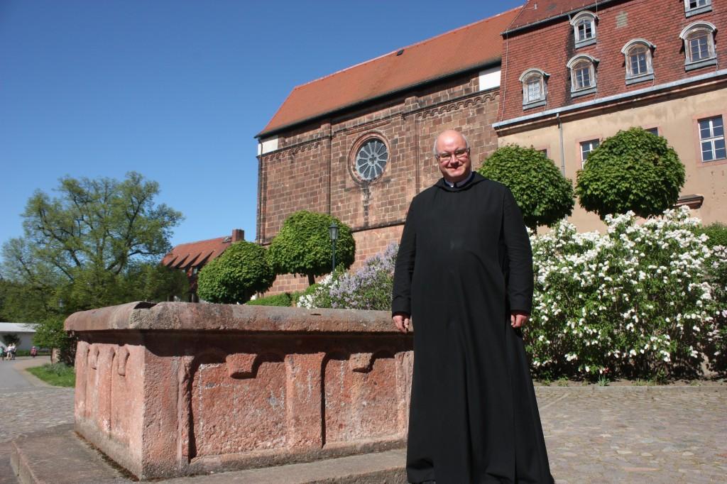 Pater Maurus Kraß, der Prior des im sächsischen Wechselburg seit 1993 beheimateten Benediktiner-Konvents, vor der Westfront der einstigen Stiftsbasilika, die heute als Pfarr- und Klosterkirche genutzt wird. Foto: Michael Kunze